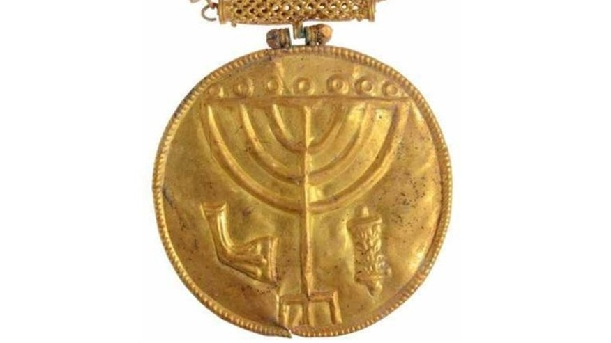 A 10-cm gold medallion discovered in Hebrew University excavations at the foot of the Temple Mount in Jerusalem. Etched into the medallion are a menorah (Temple candelabrum), shofar (rams horn) and Torah scroll.