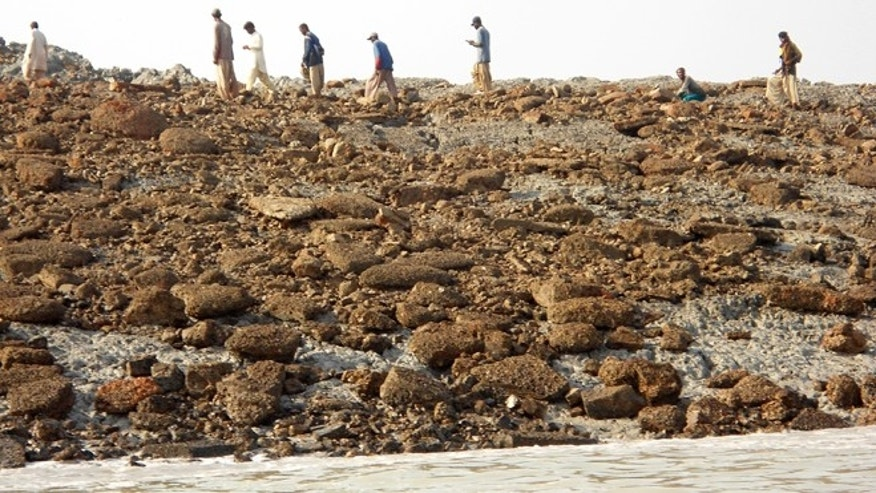 Sept. 25, 2013: People walk on an island that rose from the sea following an earthquake, off Pakistan's Gwadar coastline in the Arabian Sea.