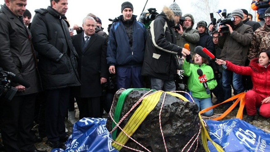 Oct. 16, 2013: People look at what scientists believe to be a chunk of the Chelyabinsk meteor, recovered from Chebarkul Lake near Chelyabinsk, about 930 miles east of Moscow.