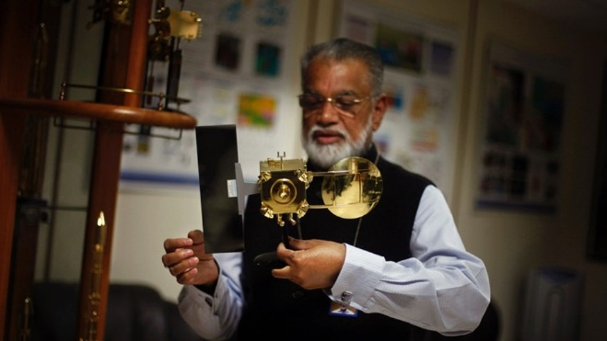 Oct. 31, 2013: Chairman of the Indian Space and Research Organization (ISRO) K. Radhakrishnan holds a model of Mars orbiter at his office in New Delhi, India.