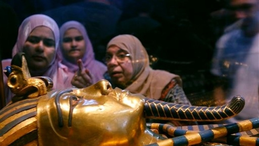 Women look at one of the coffins of King Tutankhamun at the Egyptian museum in Cairo, Egypt.