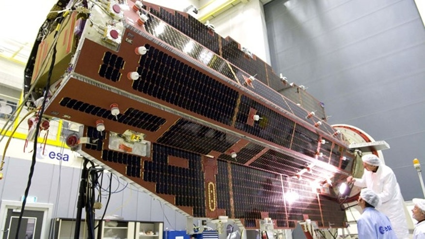 Scientists inspect the solar panels on the GOCE satellite during final testing at ESA-ESTEC in 2008.