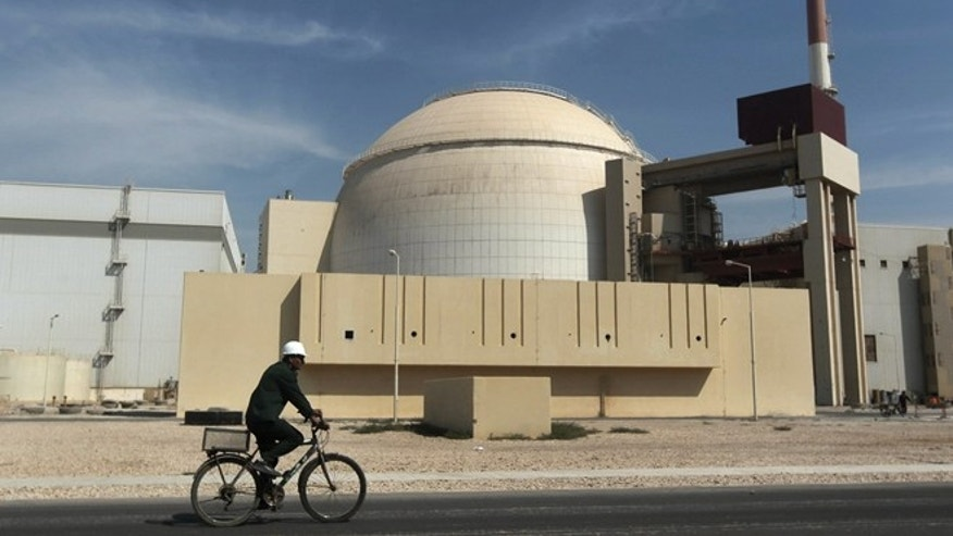 A worker rides a bicycle in front of the reactor building of the Bushehr nuclear power plant, just outside the southern city of Bushehr, Iran, in 2010.