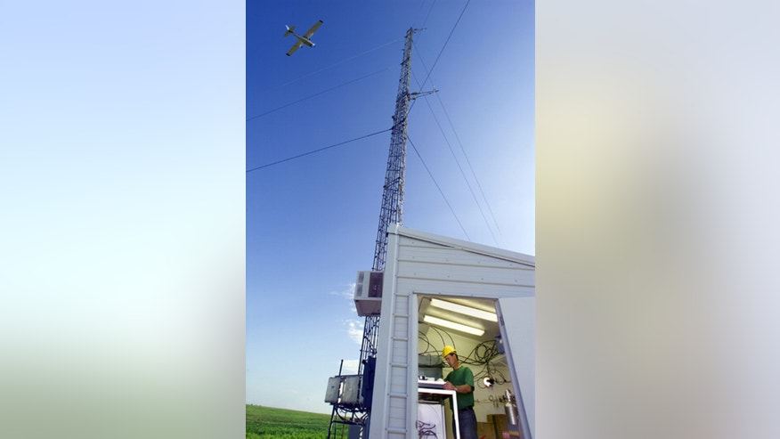 A Cessna plane, making continuous observations of carbon dioxide, flying over an Atmospheric Radiation Measurement tower used by the Energy Department near the town of Lamont, Oklahoma.