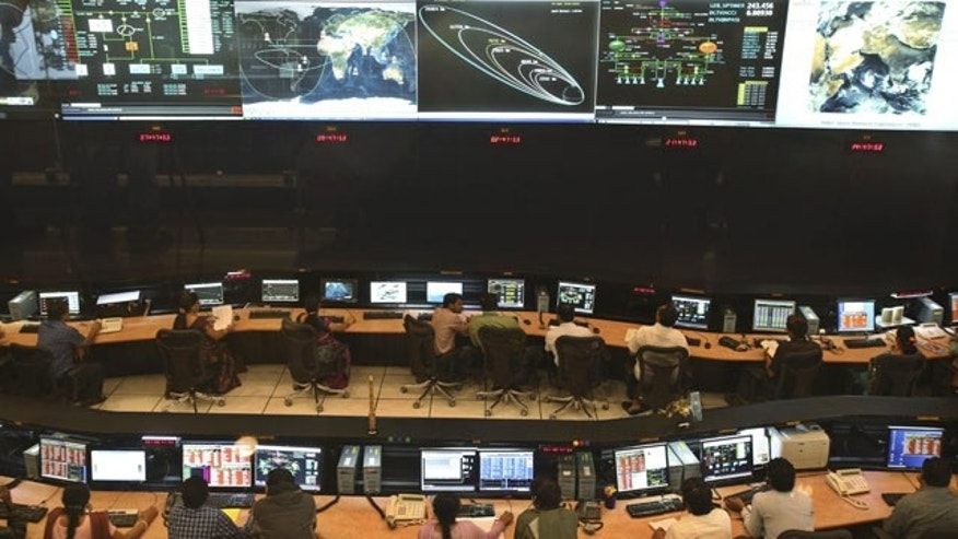 November 27, 2013: Indian Space Research Organization (ISRO) scientist and engineers monitor the movements of India's Mars orbiter at their Spacecraft Control Center in Bangalore, India. (AP Photo)