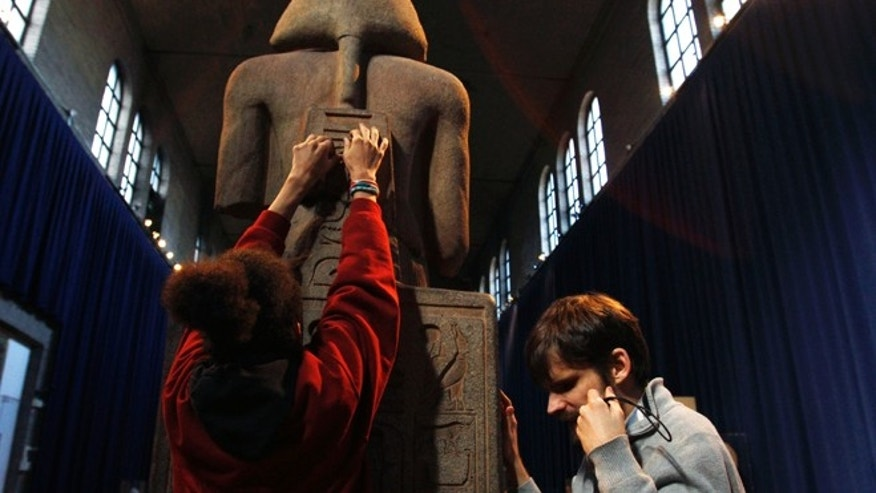 Nov. 25, 2013: Angel Ayala, left, and Austin Seraphin touch a quartzite likeness of Ramesses II at the Penn Museum in Philadelphia.