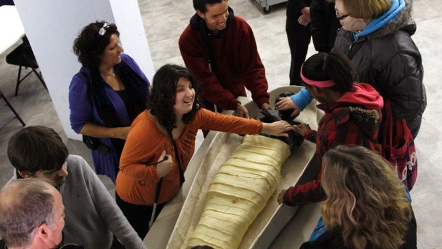 Nov. 25, 2013.: Katie Maunder, left, reaches out to touch a replica of a mummy as blind high school student Angel Ayala, 16, center, visually impaired high school student Tatyana Allen, 16, right and blind high school student Cache Ballard, 16, participate in the classroom segment of a special tour at the Penn Museum in Philadelphia.