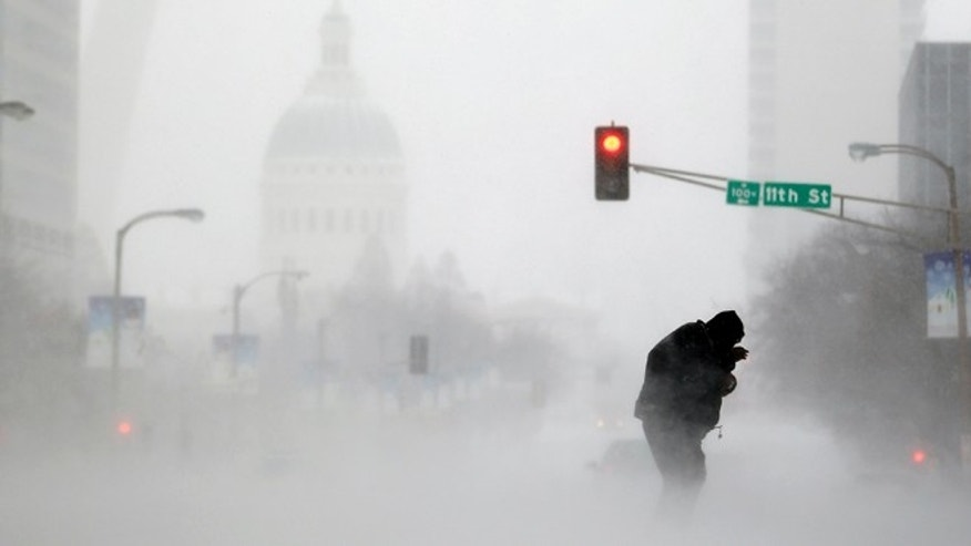 Jan. 5, 2014: A person struggles to cross a street in blowing and falling snow as the Gateway Arch appears in the distance, in St. Louis.