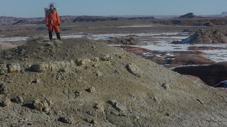 Journalist Elizabeth Howell atop a ridge, wearing a spacesuit, at Utah's Mars Desert Research Station.
