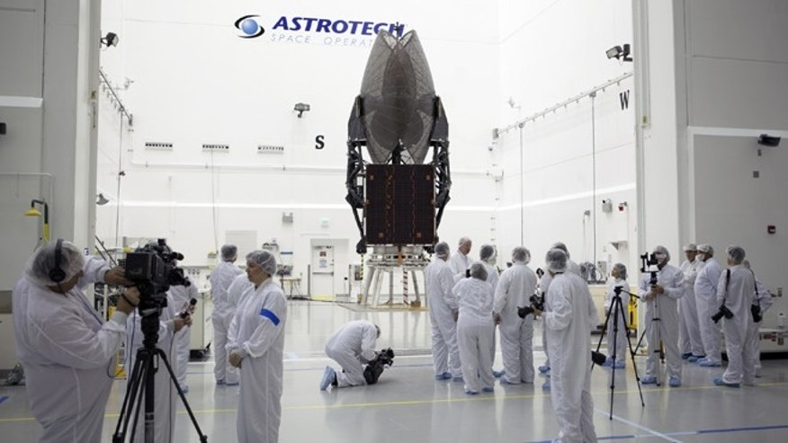 Members of the news media are given an opportunity for an up-close look at the TDRS-L spacecraft undergoing preflight processing inside the Astrotech payload processing facility in Titusville.