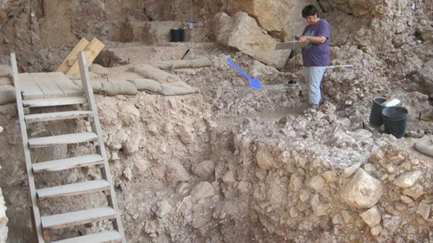 Qesem Cave near the central Israel town of Rosh Ha'ayin, with an arrow pointing to a 300,000-year-old hearth recently uncovered.