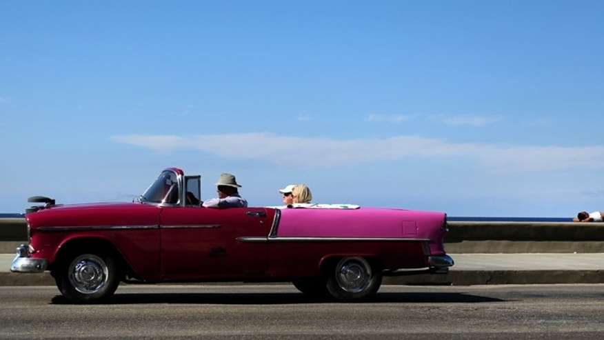 Jan. 26, 2014: Tourists ride in a classic American car that serves as a taxi in Malecon in Havana, Cuba.