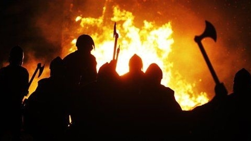 "Members of the ""Jarl Squad""  dressed in Viking costume as they gather around a burning Viking ship."