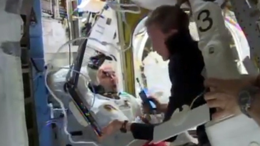 In this Tuesday, July 16, 2013 image from video made available by NASA, astronaut Karen Nyberg assists astronaut Luca Parmitano remove his space suit after an aborted spacewalk aboard the International Space Station.