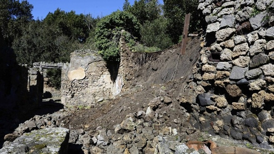 March 3, 2014: Bricks and rocks are seen on the ground after a section of wall around an ancient shop collapsed in Pompeii as a consequence of a rainstorm.