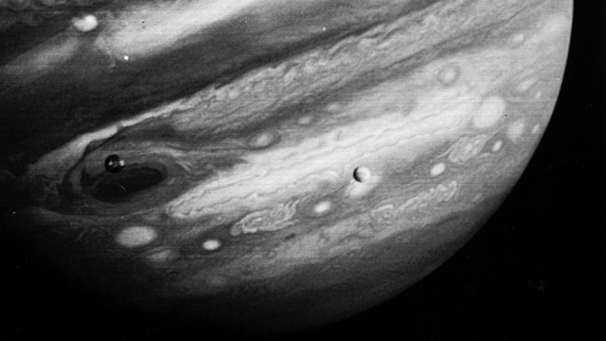 This Feb. 13, 1979 photo released by NASA's Jet Propulsion Laboratory on Feb. 22, 1979 shows the planet Jupiter and two of its moons, Io, left, and Europa, center. The Voyager 1 spacecraft was about 12.4 million miles from Jupiter when the photo was made.