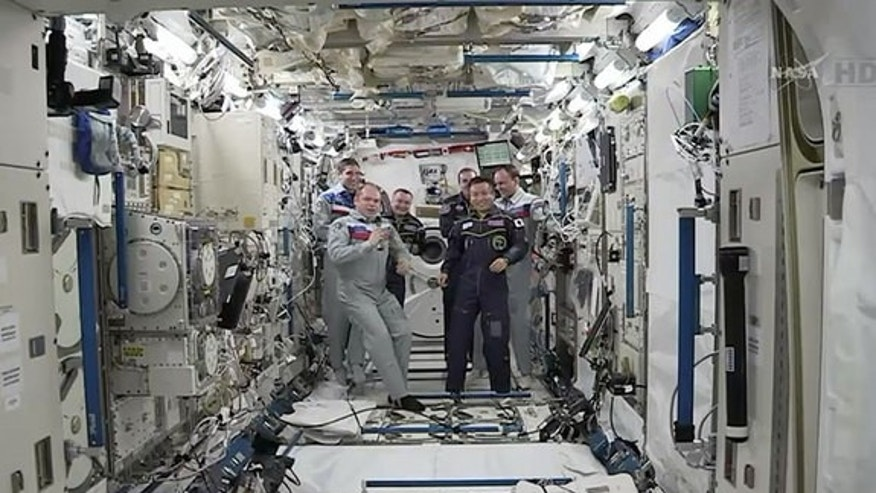 JAXA astronaut Koichi Wakata (at right) receives command of the International Space Station from Russian cosmonaut Oleg Kotov (left) during a brief ceremony held inside Japan's Kibo laboratory aboard the orbiting outpost on Sunday, March 9, 201