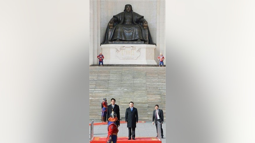 With a backdrop of a giant statue of the Mongol Empire founder Genghis Khan, Japanese Prime Minister Shinzo Abe, standing left on the podium, accompanied by his Mongolian counterpart Norov Altankhuyag, attends welcome ceremony after his arrival for a two-day visit in Ulan Bator, Mongolia, Saturday, March 30, 2013. Abe was the first Japanese leader to visit the North Asian country in almost seven years.