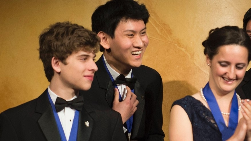 Eric S. Chen, 17, of San Diego, Calif. (center) wins the first-place prize of $100,000 in the Intel Science Talent Search, a program of Society for Science & the Public. Also pictured are finalists Alec Vadim Arshavsky of N.C. (left) and Kathy Camenzind (right) of Calif.