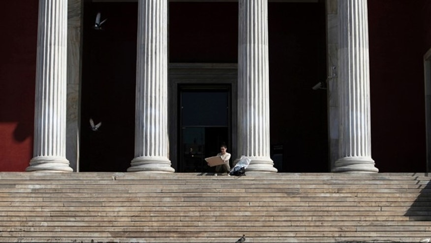 March 13, 2014: An architecture student checks a drawing on the steps of the National Archaeological Museum in Athens. The 125-year old Archaeological Museum is the biggest in Greece, displaying more than 11,000 artifacts from Neolithic to Roman times.