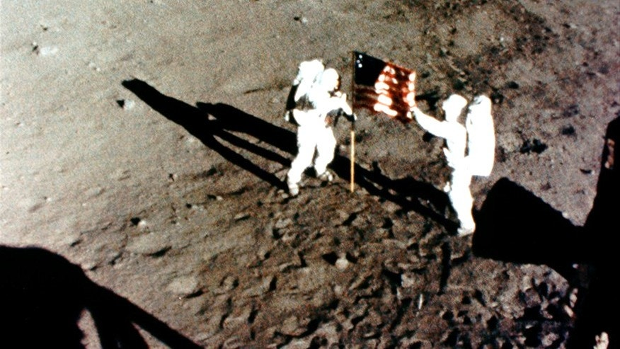 Buzz Aldrin and Neil Armstrong plant US flag on the moon surface during Apollo 11 mission.