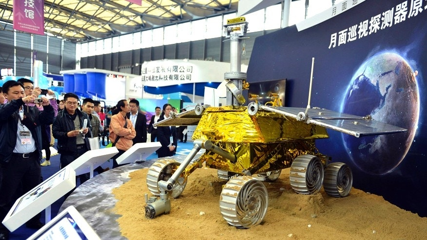 Visitors take pictures of a prototype model of a lunar rover at the 15th China International Industry Fair in Shanghai, November 5, 2013. China will land its first probe on the moon in early December which will deploy a buggy to explore its surface, an official said on November 26, marking a major milestone in the country's space ambitions.