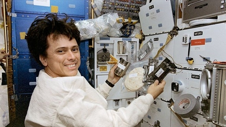 Franklin Chang Diaz, seen onboard the space shuttle Columbia in 1996, prepares a meal while floating weightless in space.
