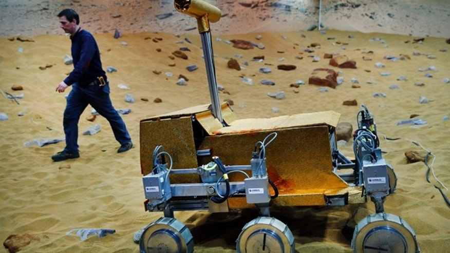 March 27, 2014: Engineer Ben Nye walks past a robotic vehicle on the 'Mars Yard Test Area', a testing ground for the robotic vehicles of the European Space Agencys ExoMars program scheduled for 2018, in Stevenage, England.