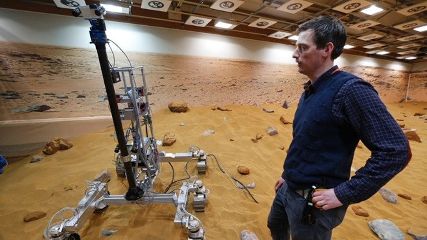 March 27, 2014: Engineer Ben Nye stands next to a robotic vehicle on the 'Mars Yard Test Area', a testing ground for the robotic vehicles of the European Space Agencys ExoMars program scheduled for 2018, in Stevenage, England.