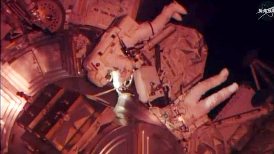 April 23, 2014: In this image made from video provided by NASA, astronauts Rick Mastracchio and Steven Swanson exit an airlock from the International Space Station. The spacewalk was scheduled to replace a dead computer and get their orbiting home back up to full strength.