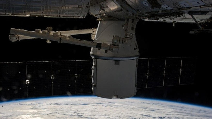 In this photo provided by NASA, the SpaceX Dragon capsule is berthed at the International Space Station Sunday April 20, 2014 as photographed by the Expedition 39 crew members onboard the orbital outpost. Two NASA astronauts aboard the International Space Station will conduct a spacewalkWednesday April 23, 2014 to replace a failed backup computer relay system on the space station's truss. (AP Photo/NASA)