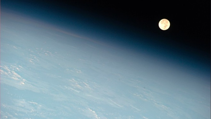 May 17, 2011: The moon appears near the earth's horizon in this photograph of an orbital moonset taken from aboard the International Space Station.