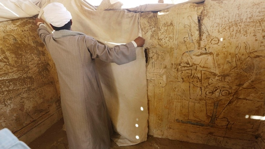 An Egyptian archeology worker covers limestones at a newly-discovered tomb in Egypt.