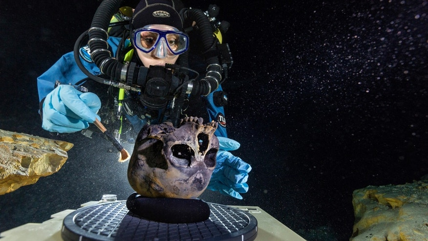FILE: Diver Susan Bird, working at the bottom of Hoyo Negro, a large dome-shaped underwater cave in Mexico's Yucatan Peninsula, brushes a human skull found at the site while her team members take detailed photographs.