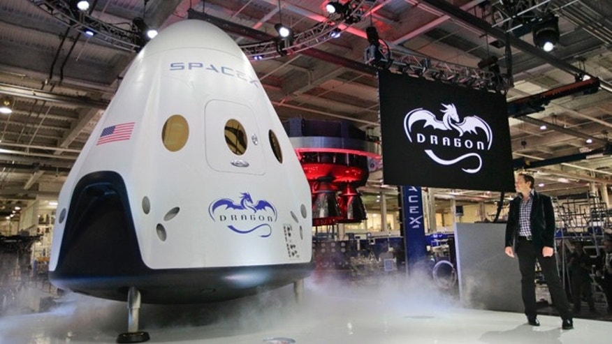 May 29, 2014: Elon Musk, right, unveils the SpaceX Dragon V2 spacecraft in Hawthorne, Calif. SpaceX, which has flown unmanned cargo capsules to the International Space Station, unveiled the new spacecraft Thursday designed to ferry up to seven astronauts to the space station. (AP/Jae C. Hong)