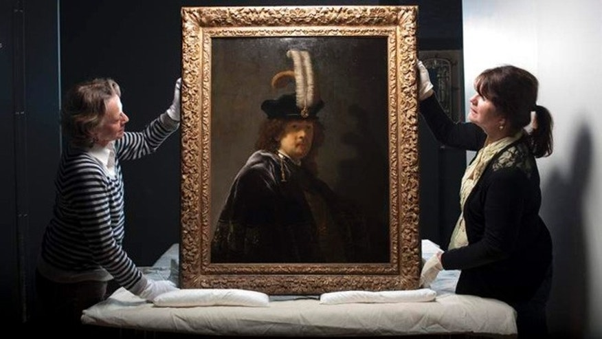 June 9, 2014: Conservators hold up a recently verified 1635 self-portrait by Dutch artist Rembrandt van Rijn (Courtesy Press Association)