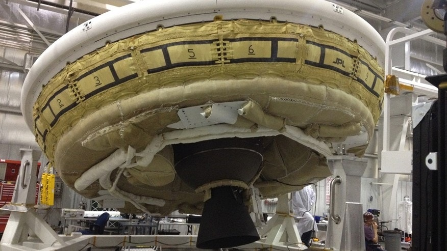 In this undated image provided by NASA a saucer-shaped test vehicle holding equipment for landing large payloads on Mars is shown in the Missile Assembly Building at the US Navy's Pacific Missile Range Facility in Kauai, Hawaii.