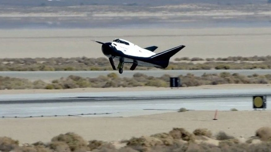 Dream Chaser space plane built by Sierra Nevada Corp. landed with its left landing gear undeployed in this still from an Oct. 26, 2013, unmanned drop test at Edwards Air Force Base in California. The malfunction caused the prototype to skid off