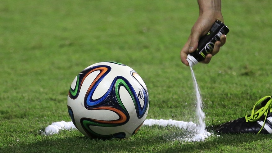 In this  June 6, 2014, photo, a referee uses vanishing spray during a referee's training session in Rio de Janeiro, Brazil. Referees will use vanishing spray during 2014 World Cup to stop defensive walls creeping forward at free-kicks. The international soccer tournament is set to begin in a few days, with Brazil and Croatia competing in the opening match on June 12. (AP Photo/Hassan Ammar)