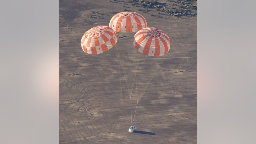 A test version of NASA's Orion spacecraft touches down in the Arizona desert after its most complicated parachute test to date.