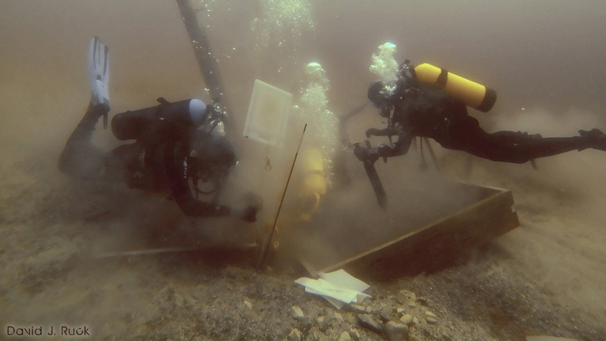 In this June 16, 2013 photo provided by Great Lakes Exploration Group, divers inspect a hole being dug beside a wooden beam jutting from the floor of Lake Michigan during  exploration for the 17th century ship the Griffin.