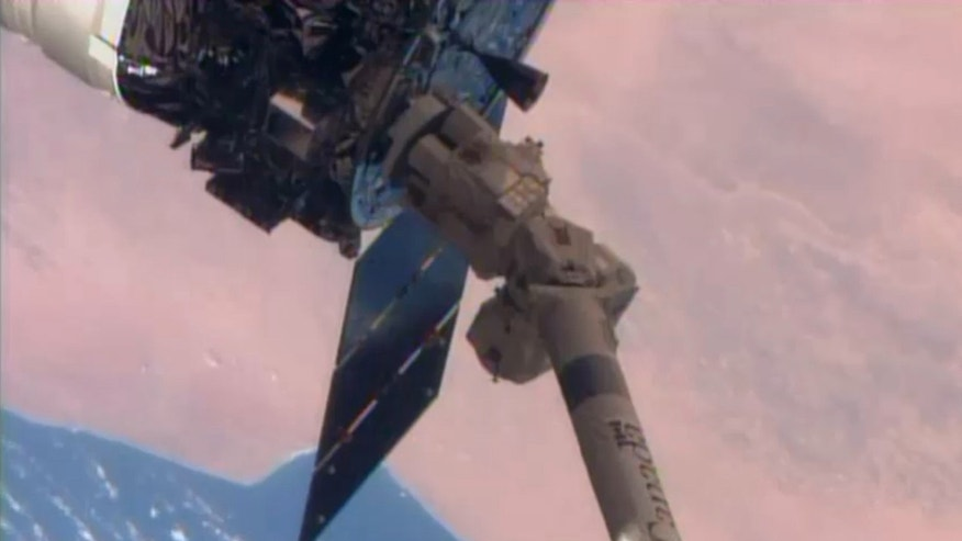 In this image from NASA-TV shows the Cygnus cargo spacecraft as it is grappled by the International Space Station's Canadarm.