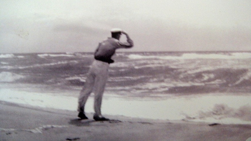 In this 1930s photo provided by the Hendrickson family, Richard Hendrickson leans into the wind as a storm hits a Long Island, N.Y. beach.