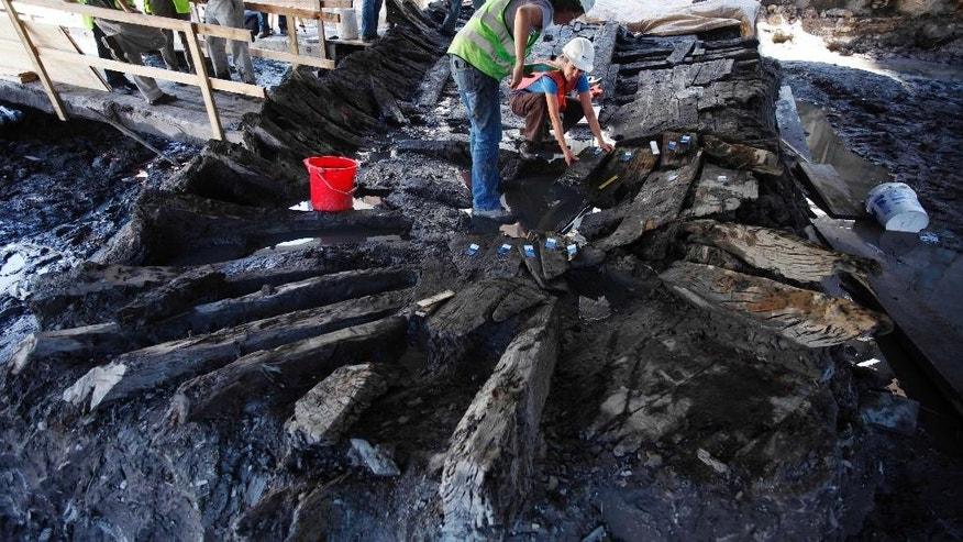 FILE- In this July 27, 2010, file photo, a pair of archeologists begin dismantling the remains of an 18th century ship at the World Trade Center construction site in New York. Columbia University scientists say this week they have determined wood used in the ship's frame came from a Philadelphia-area forest in 1773, before the signing of the Declaration of Independence and the Revolutionary War. (AP Photo/Mark Lennihan, File)
