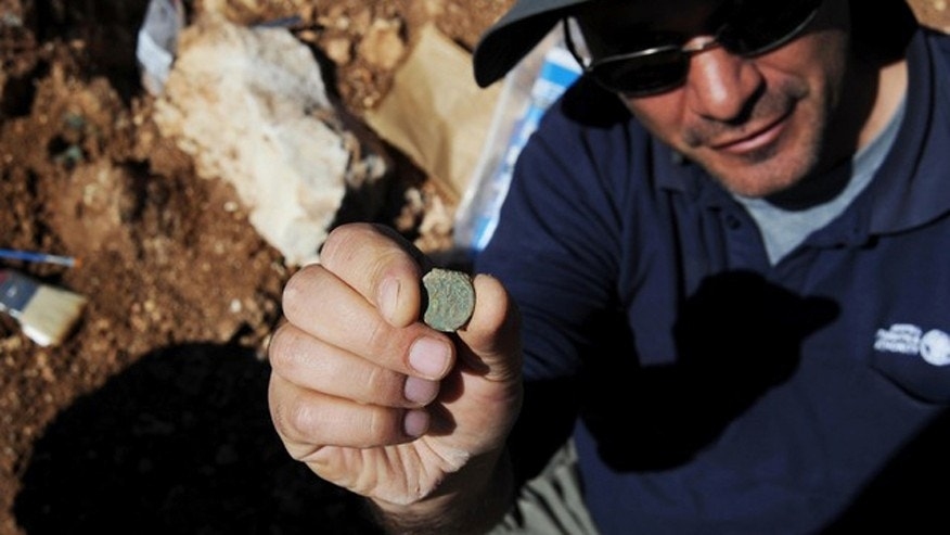 Pablo Betzer, IAA District Archaeologist for Judah, with a coin from the Year Four of the Great Revolt.