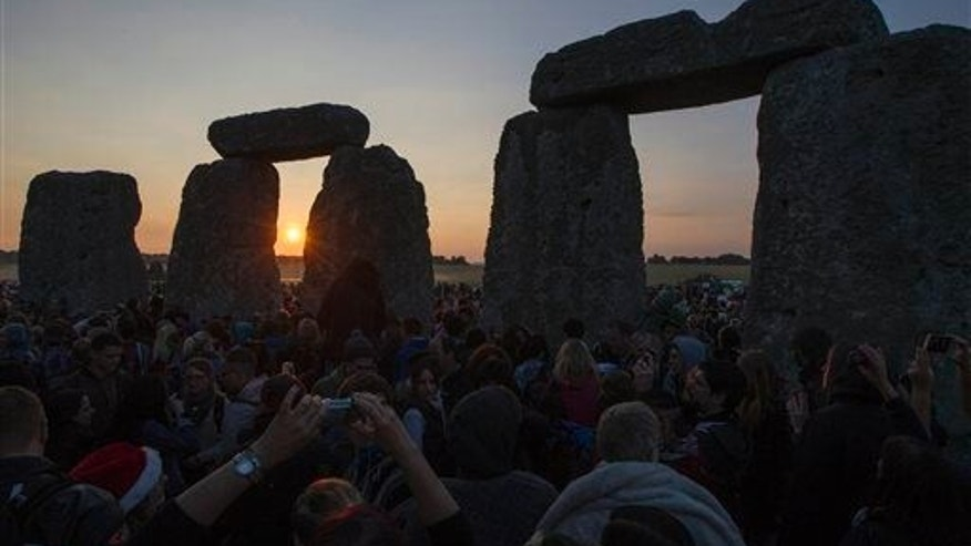 The sun rises as thousands of revelers gathered at the ancient stone circle Stonehenge, near Salisbury, England, to celebrate the summer solstice, the longest day of the year on June 21, 2014.