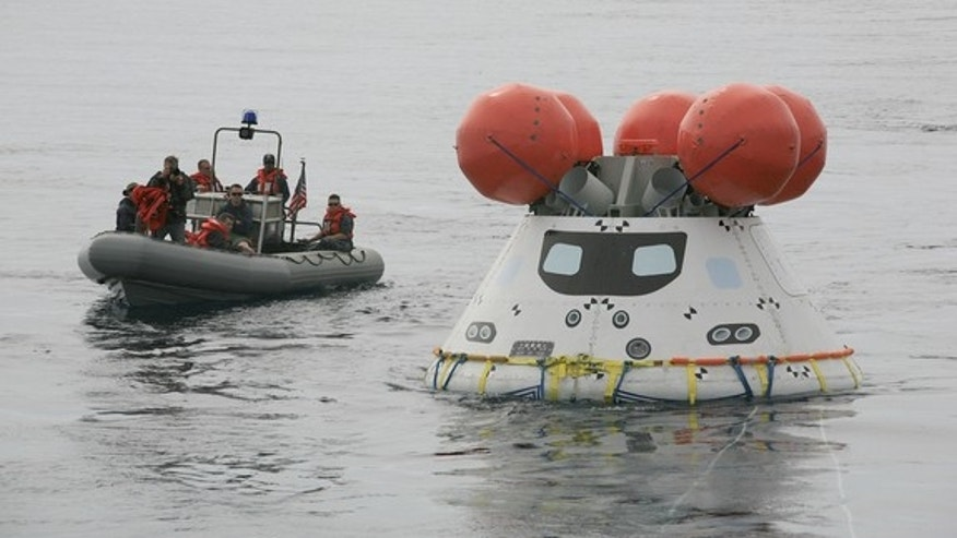 A U.S. Navy boat approaches NASA's Orion space capsule off the coast of San Diego, California, during Pacific Ocean recovery tests on Aug. 2, 2014.