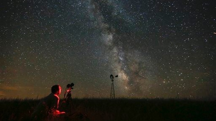 Omaha photographer Lane Hickenbottom photographs the night sky in a pasture near Callaway, Neb.