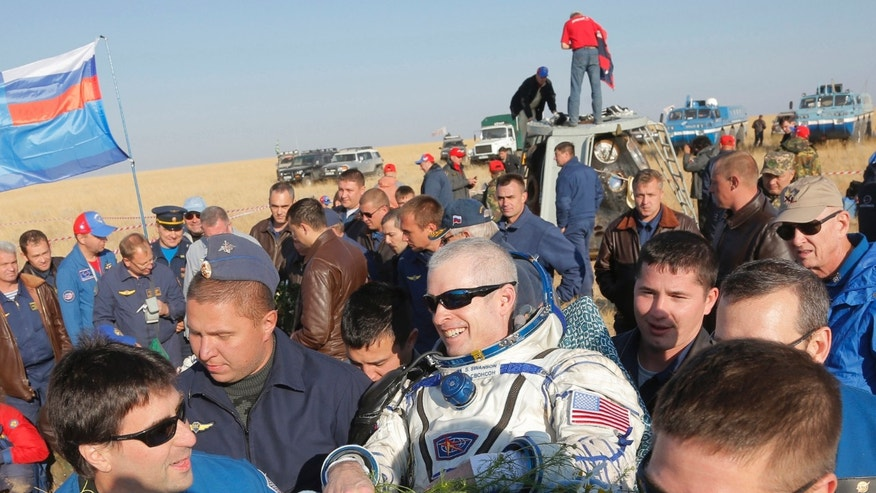 NASA specialist with Russian search and rescue team members carry U.S. NASA astronaut Steven Swanson after returning to the earth Thursday, Sept. 11.