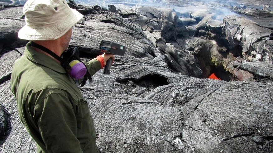 This Monday, Sept. 15, 2014, photo provided by the U.S. Geological Survey shows a geologist from the Hawaiian Volcano Observatory using a radar gun to measure the speed of the lava flow from the June 27th flow from the Kilauea volcano in Pahoa, Hawaii. On Tuesday, Sept. 16, 2014, Hawaii County spokesman Kevin Dayton said the slow-moving lava is expected to bypass homes in the Kaohe Homesteads subdivision, and the lava is about 19 days from reaching Pahoa Village Road. (AP Photo/U.S. Geological Survey)